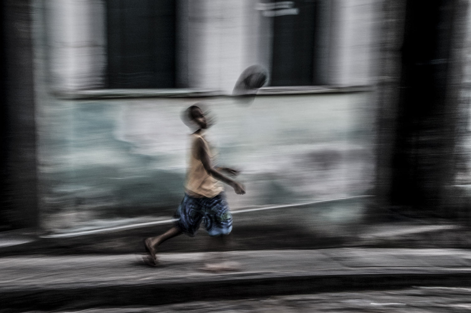 Boy plays soccer at a street in Salvador, Bahia.
