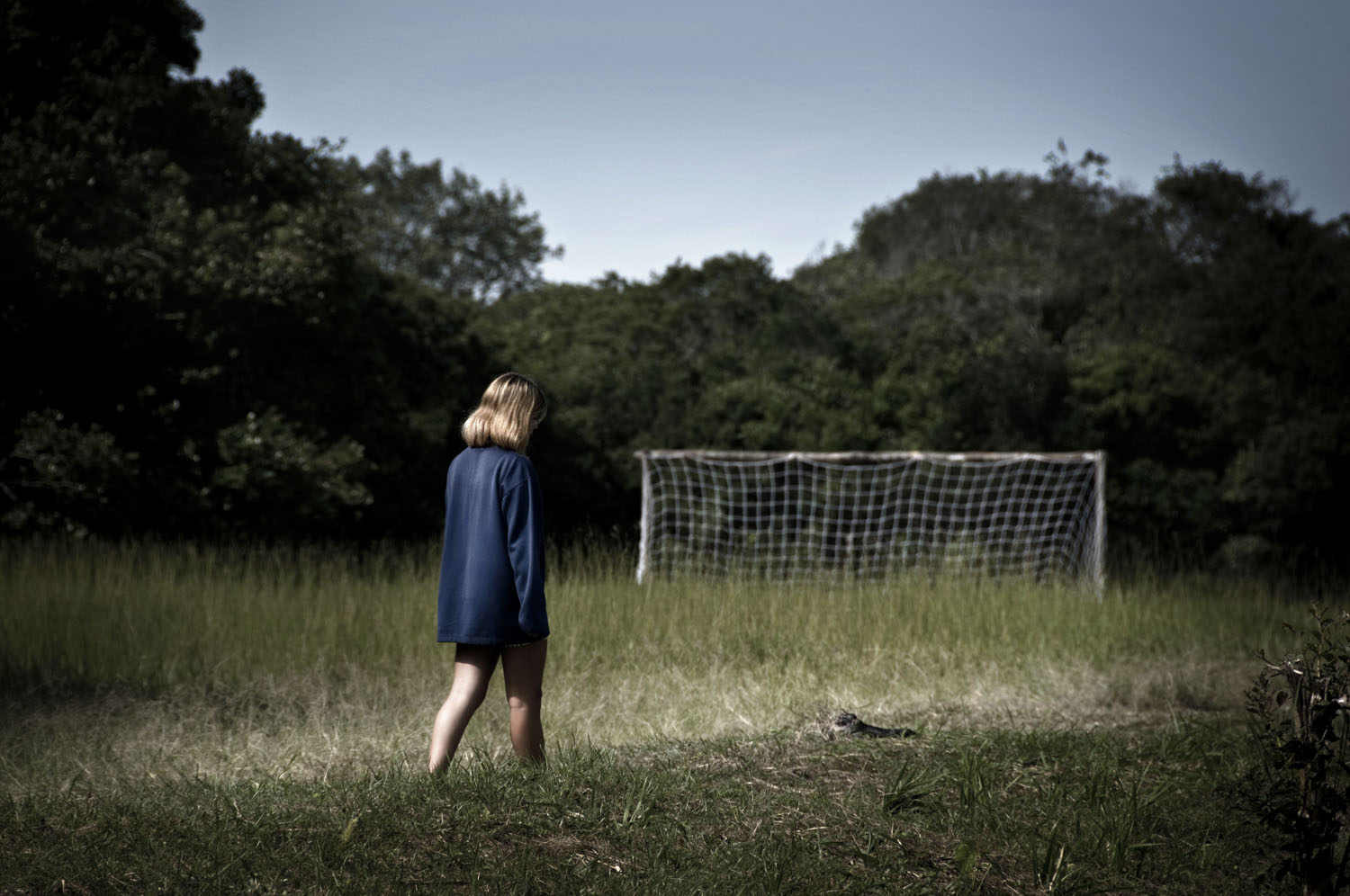 Woman walks past a soccer field, Santos.