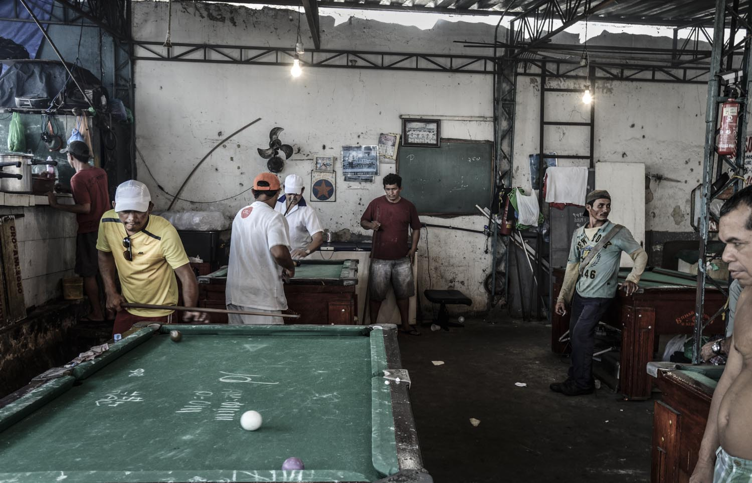 Men play pool at a local bar, Amazon, Brazil.
