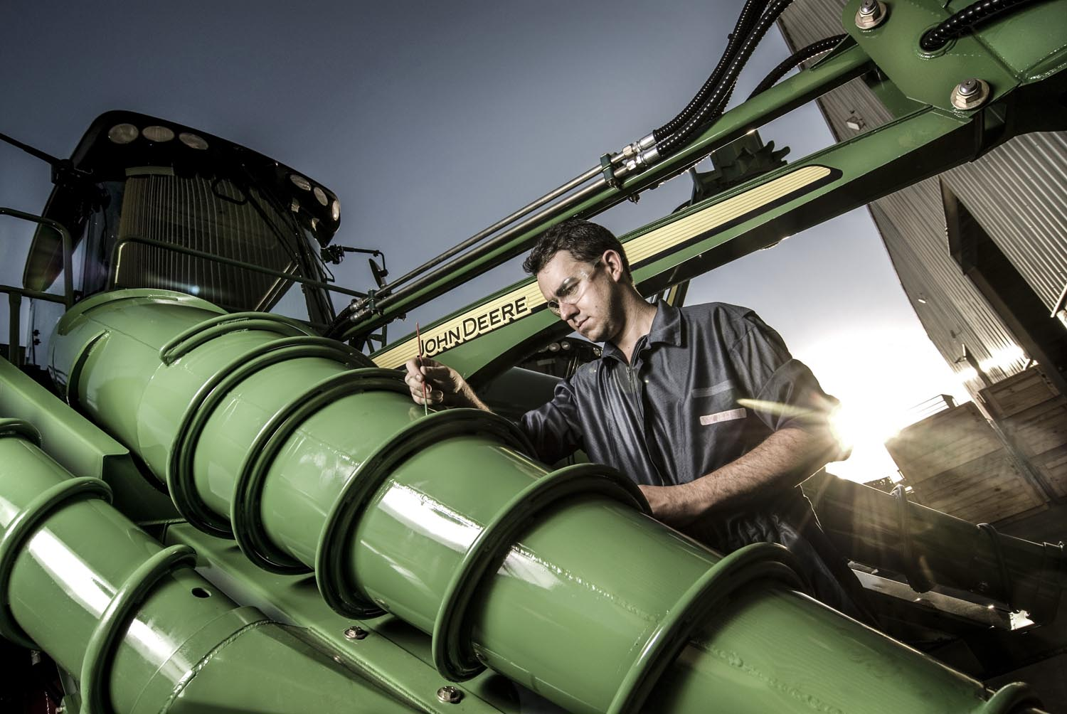 John Deere's Anual Report :Waldeir Ferreira works with final painting details of the 3510 Sugarcane Harverster at John Deere Factory.